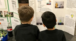 Children reading science fair projects at Enders Salk