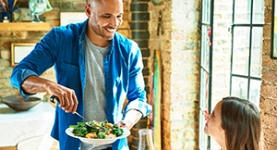 Man serving healthy bowl of food to woman