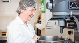 Food technician in hairnet by industrial equipment